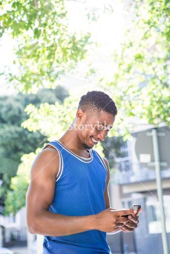 An handsome athlete using his phone