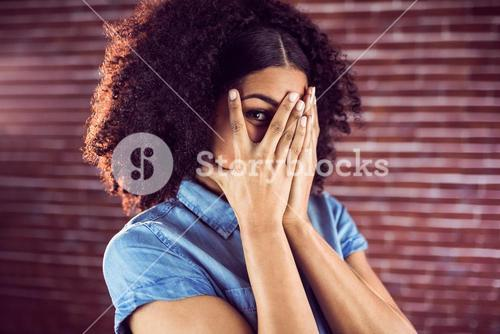 Attractive young woman hiding behind hands