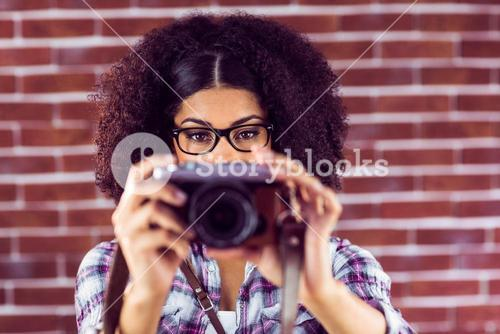 Attractive hipster taking pictures with camera