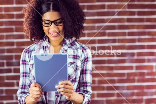 Attractive hipster smiling and looking at tablet
