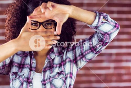 Attractive hipster taking picture with hands