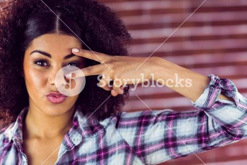 Attractive young woman showing peace sign