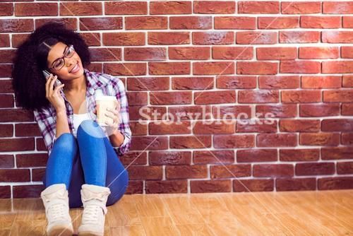 Attractive hipster sitting and phoning with smartphone
