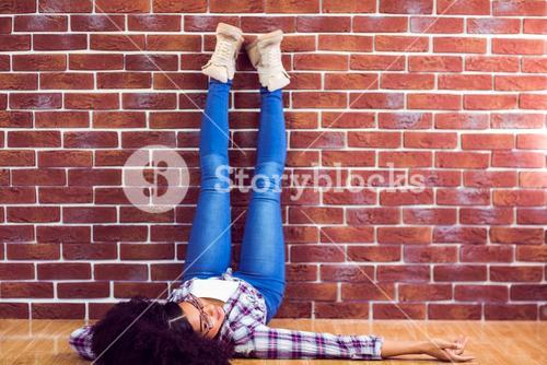 Attractive hipster lying on ground and holding legs up