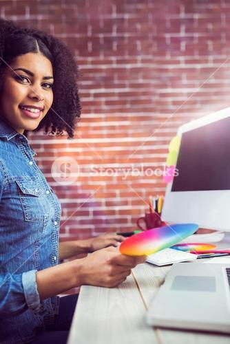 Casual female designer smiling and holding colour chart