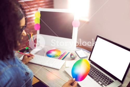 Casual female designer looking at colour chart