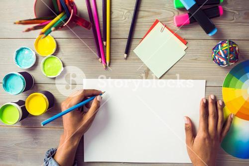 Graphic designer drawing on sheet of paper