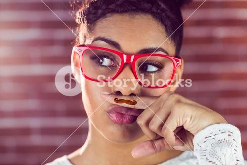 Happy hipster wearing a fake mustache
