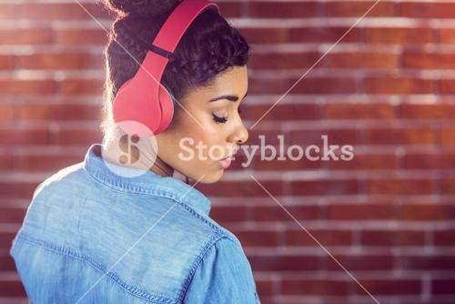 Pretty young woman with headphones looking back