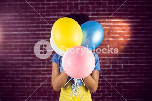Young woman hiding behind balloons
