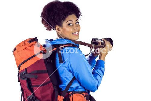 Portrait of a young woman with backpack taking picture