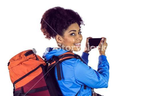 Portrait of a young woman with backpack looking back
