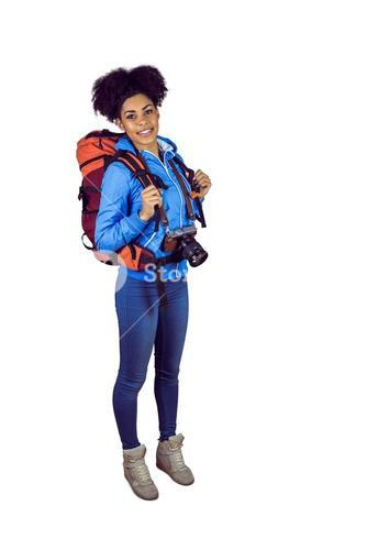 Portrait of a young woman with camera and backpack