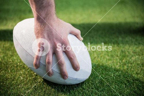 A rugby player posing a rugby ball