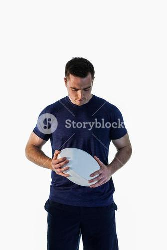 Attentive man holding a rugby ball