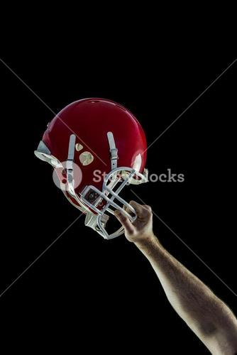 American football player holding up his helmet