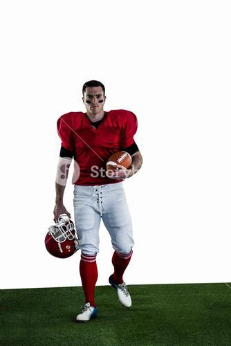 Portrait of american football player walking and holding football and helmet