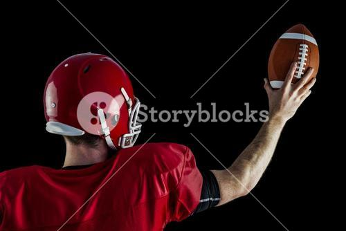 Rear view of american football player holding up football