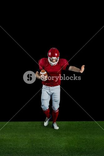American football player wrestling through and protecting football