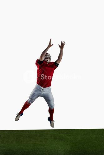 American football player trying to catch football