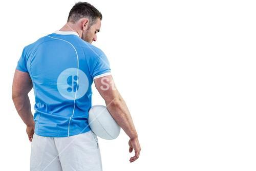 Rugby player standing with ball