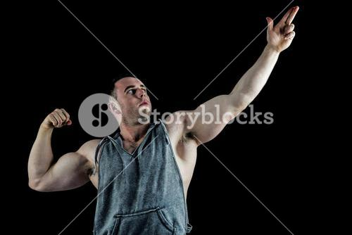 Handsome bodybuilder posing with arms up