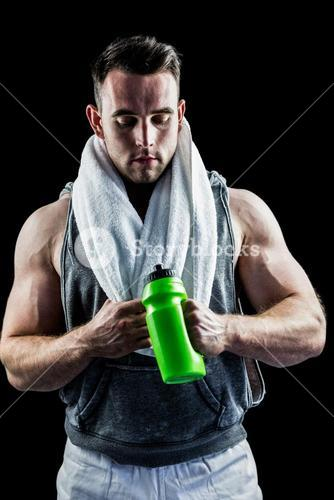 Handsome bodybuilder with towel and bottle