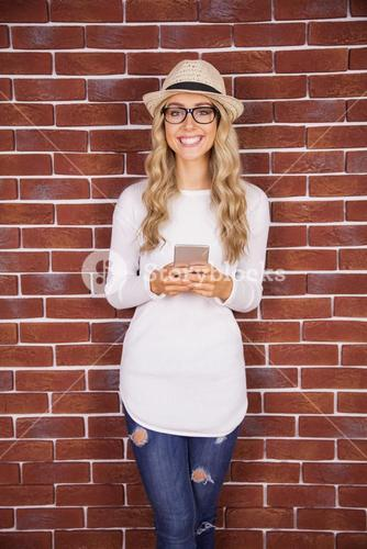 Gorgeous smiling blonde hipster with smartphone