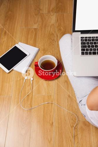 Overhead shot of laptop, tablet, coffee and headphones