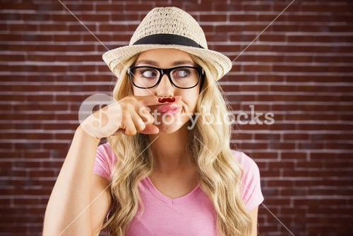 A beautiful hipster having a fake mustache