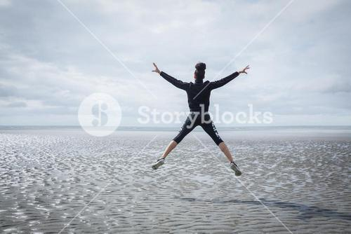 Fit girl leaping on cold day