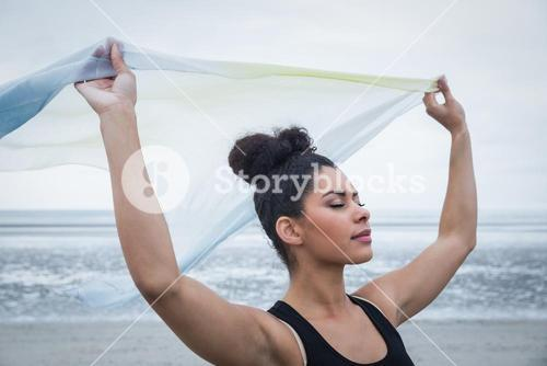 Fit girl standing with scarf blowing in wind