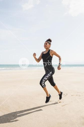 Fit woman jogging on the sand