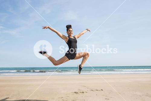 Fit woman leaping on the sand