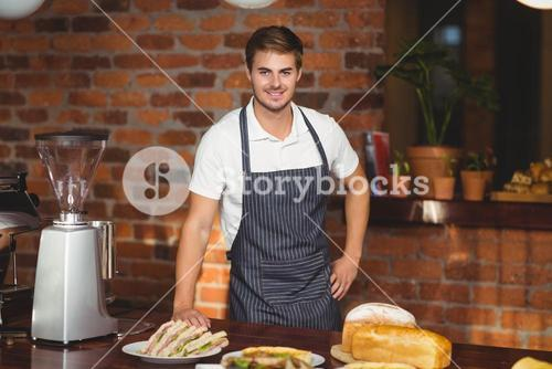 Handsome waiter bended over a food table