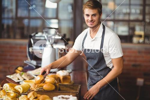 Handsome waiter picking up a roll