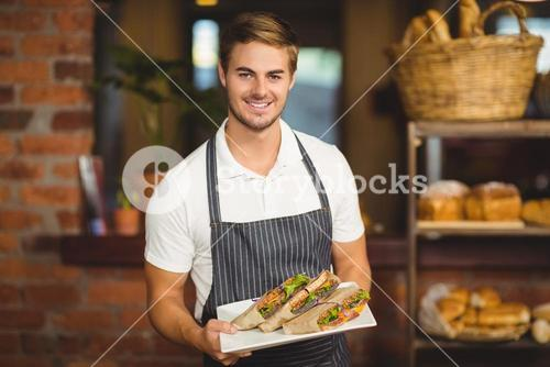 Handsome waiter holding a plate of sandwiches