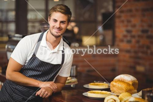 Handsome waiter leaning on a food table