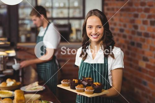 Pretty waitress holding a tray of muffins