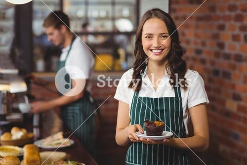 Pretty waitress holding a plate with muffin