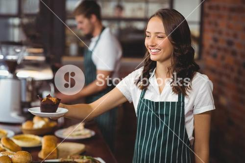 Smiling waitress serving a muffin