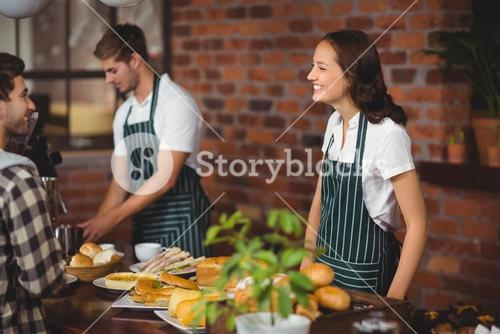 Pretty waitress talking with a customer