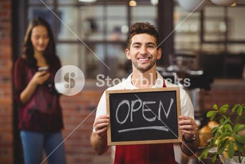 Smiling waiter posing with a chalkboard open sign