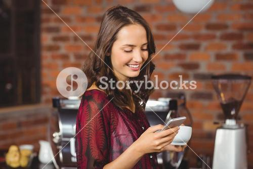 Pretty woman holding a cup of coffee and texting