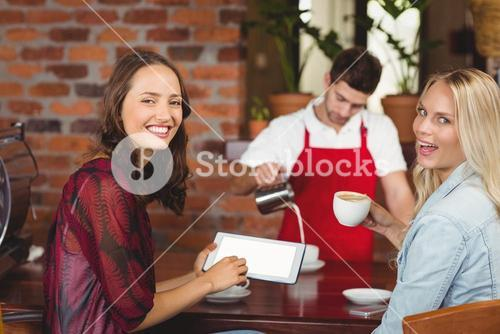 Handsome waiter preparing a cup of coffee