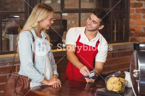 Smiling waiter swiping the credit card