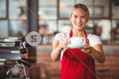 Pretty barista handing a cup of coffee