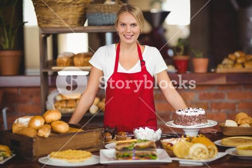 Pretty waitress bended over a food table