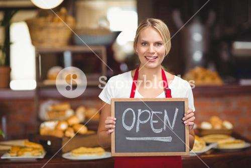 Pretty waitress with a chalkboard open sign