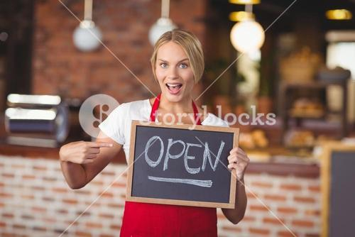 Pretty waitress pointing the chalkboard open sign